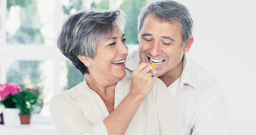 Retired couple with dental veneers smiles while feeding each other snacks in the kitchen